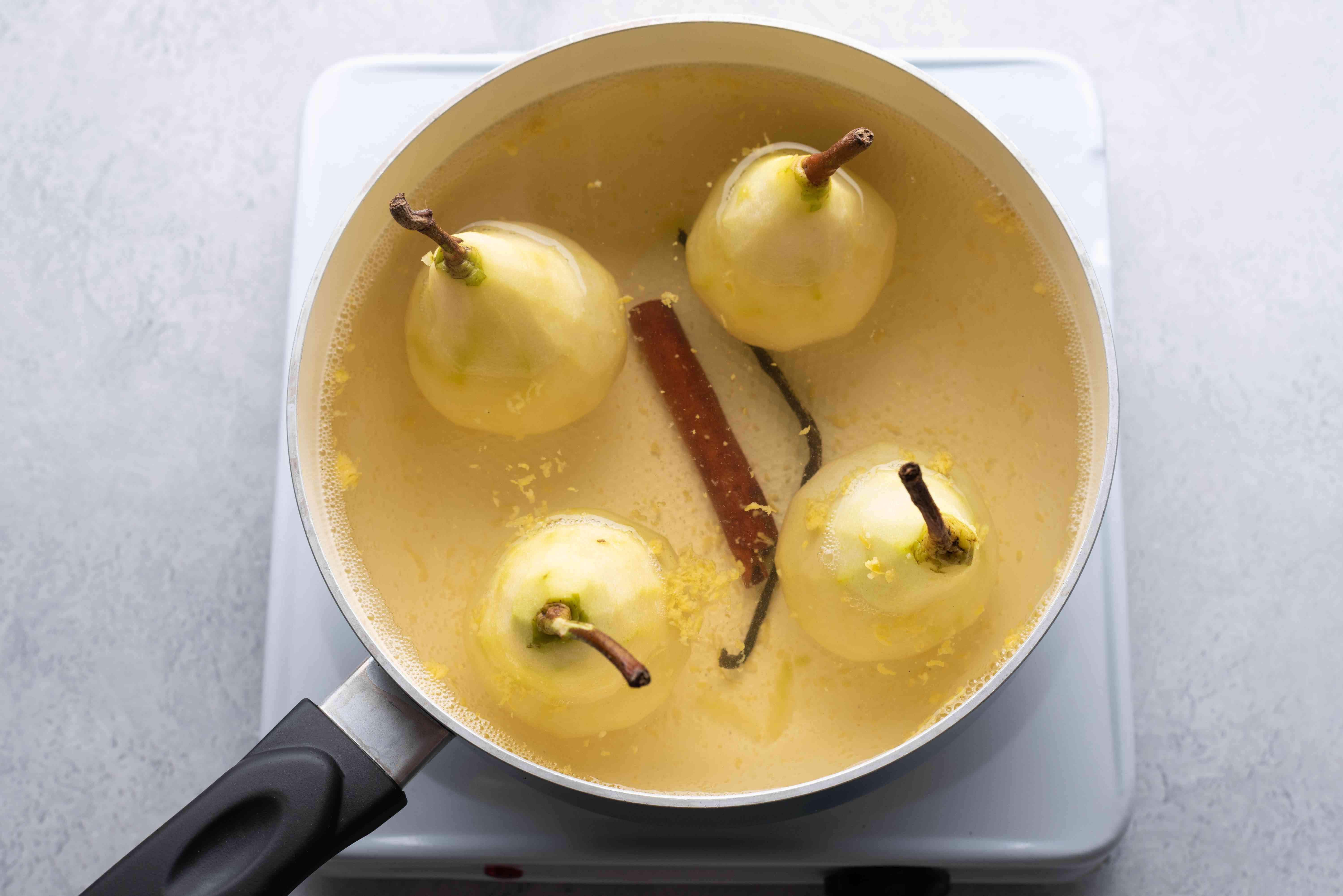 pears poaching in the white wine mixture