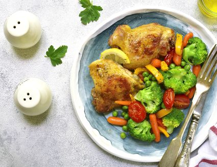 Grilled chicken thigh garnished with vegetables