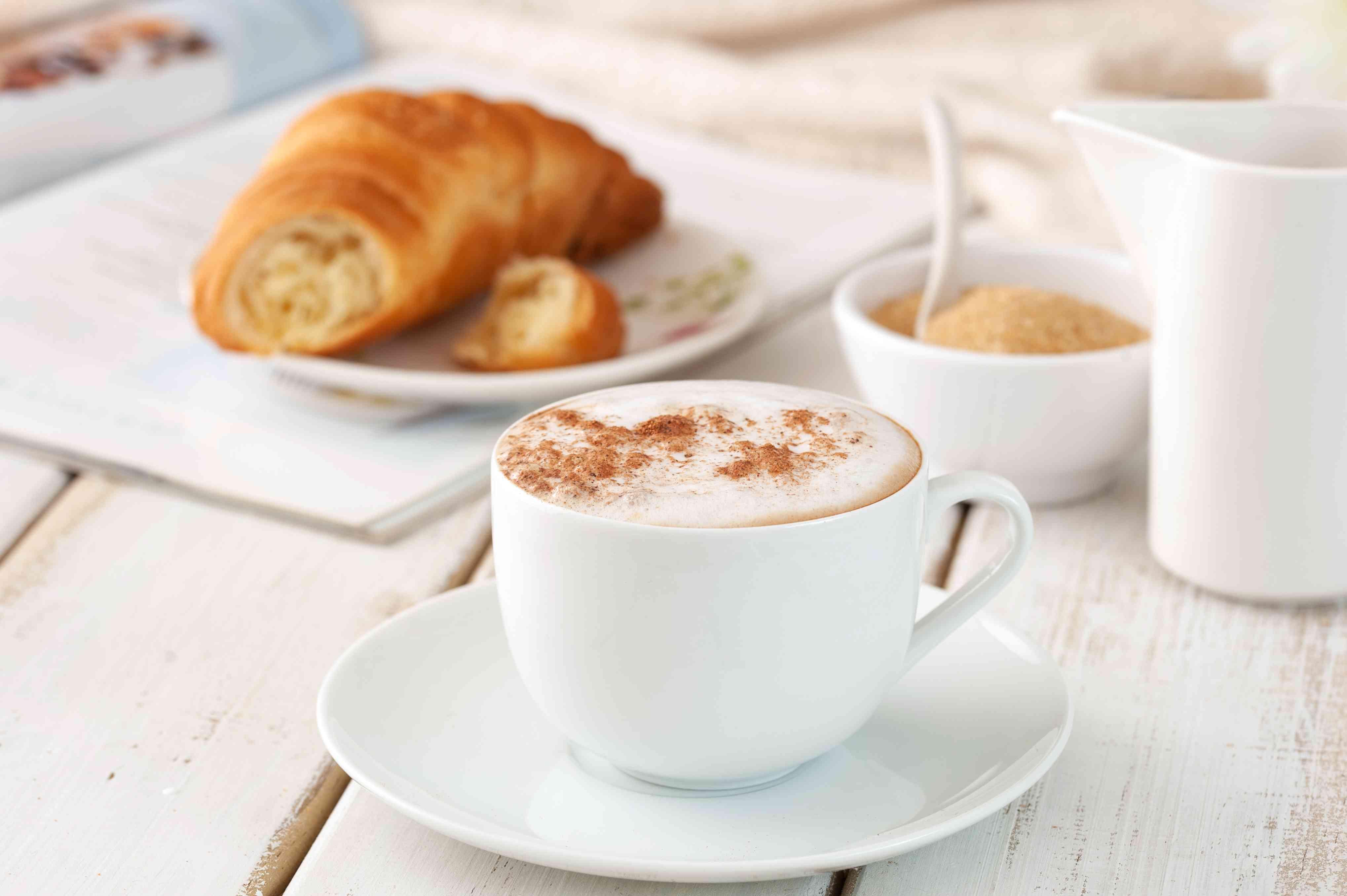 Serving café au lait sprinkled with cinnamon