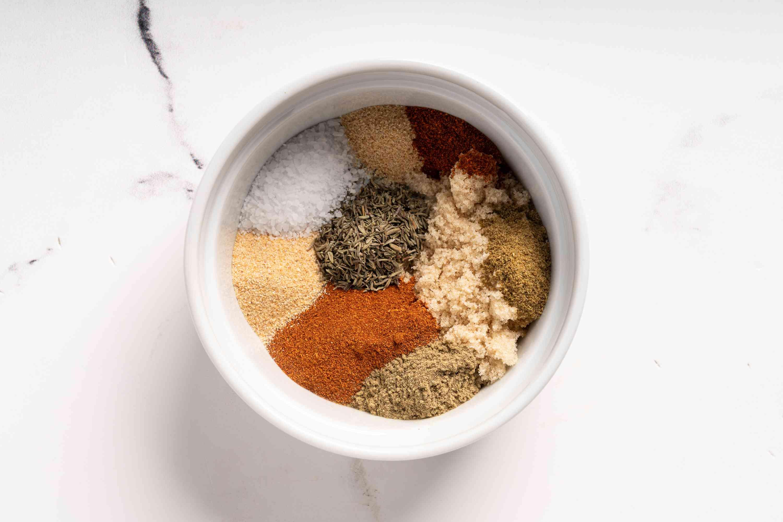 combine brown sugar, paprika, onion powder, thyme, salt, garlic powder, sage, cayenne pepper, and cumin