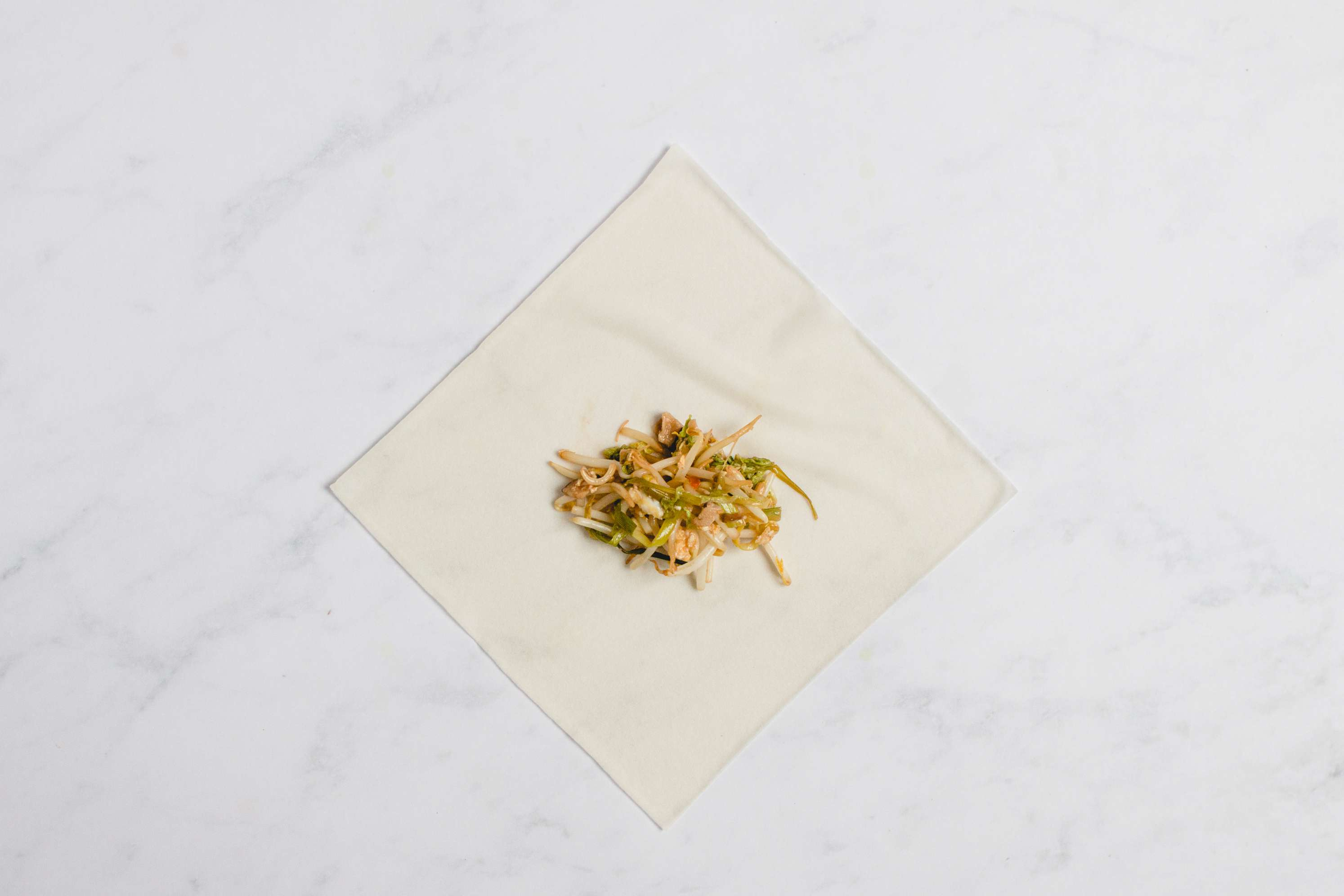 vegetable mixture on top of egg roll wrapper