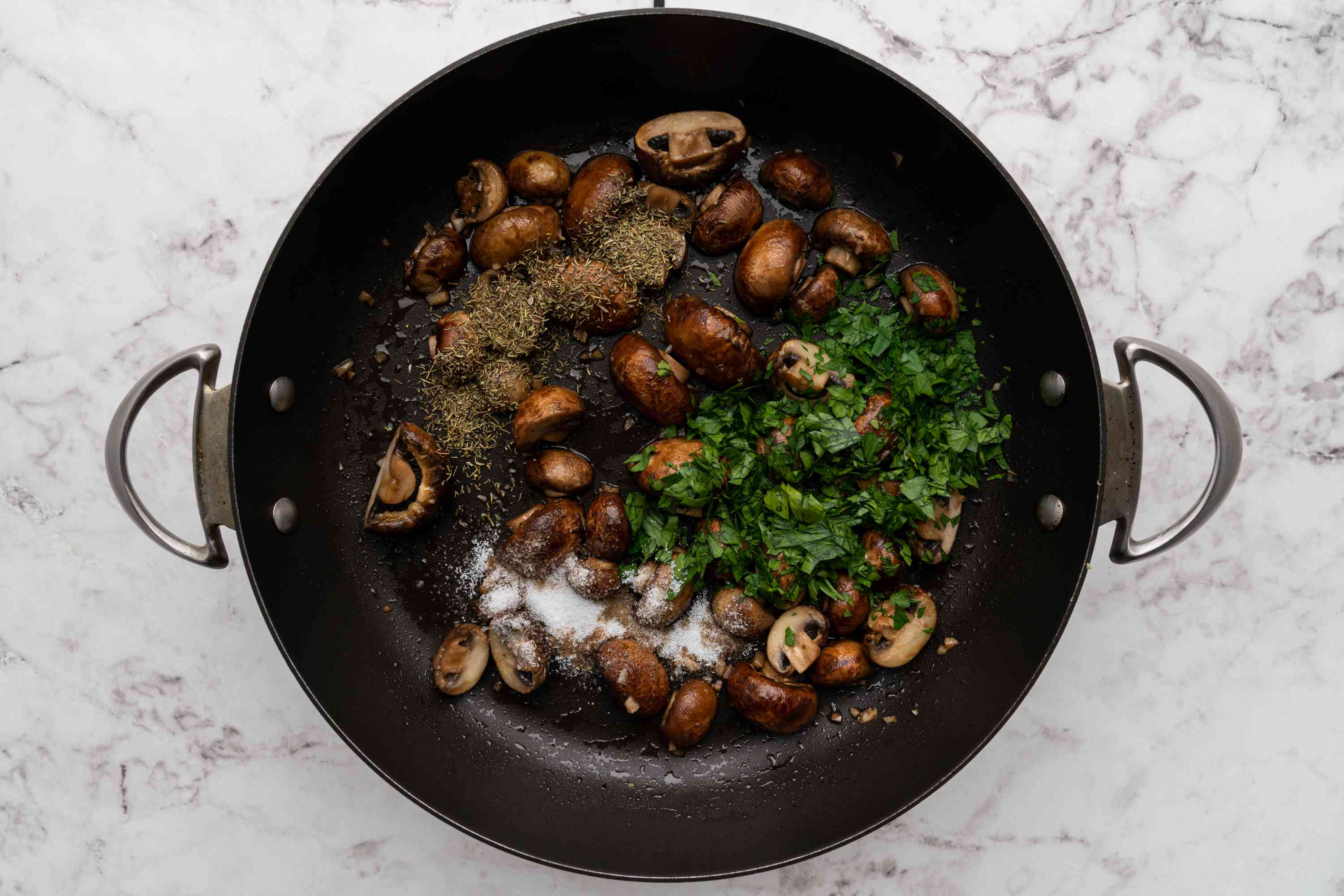 mushrooms with dried thyme, fresh parsley, and salt in a pan