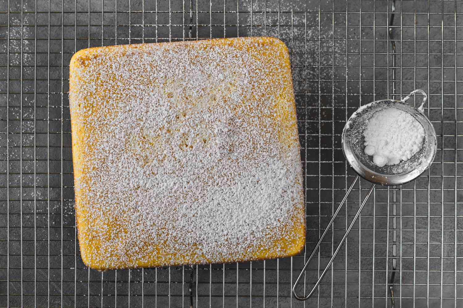 Small Cake From Half of a Box of Cake Mix with powdered sugar on top on a cooling rack