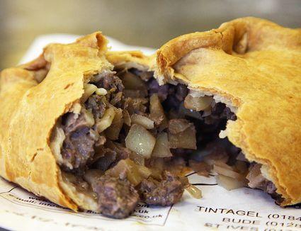 Cornish pasty broken open on newspaper