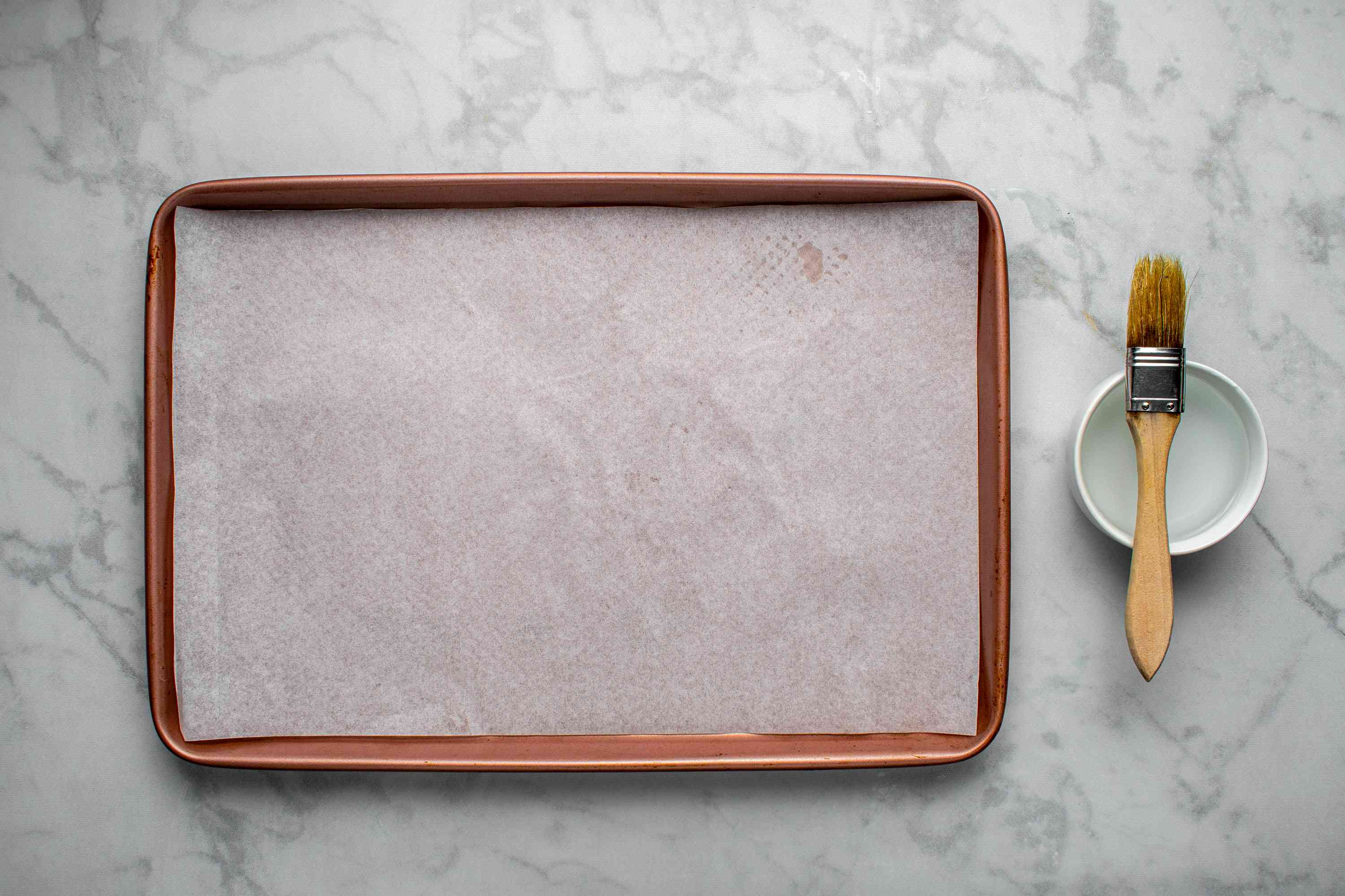 parchment paper lined baking sheet, bowl with water and brush