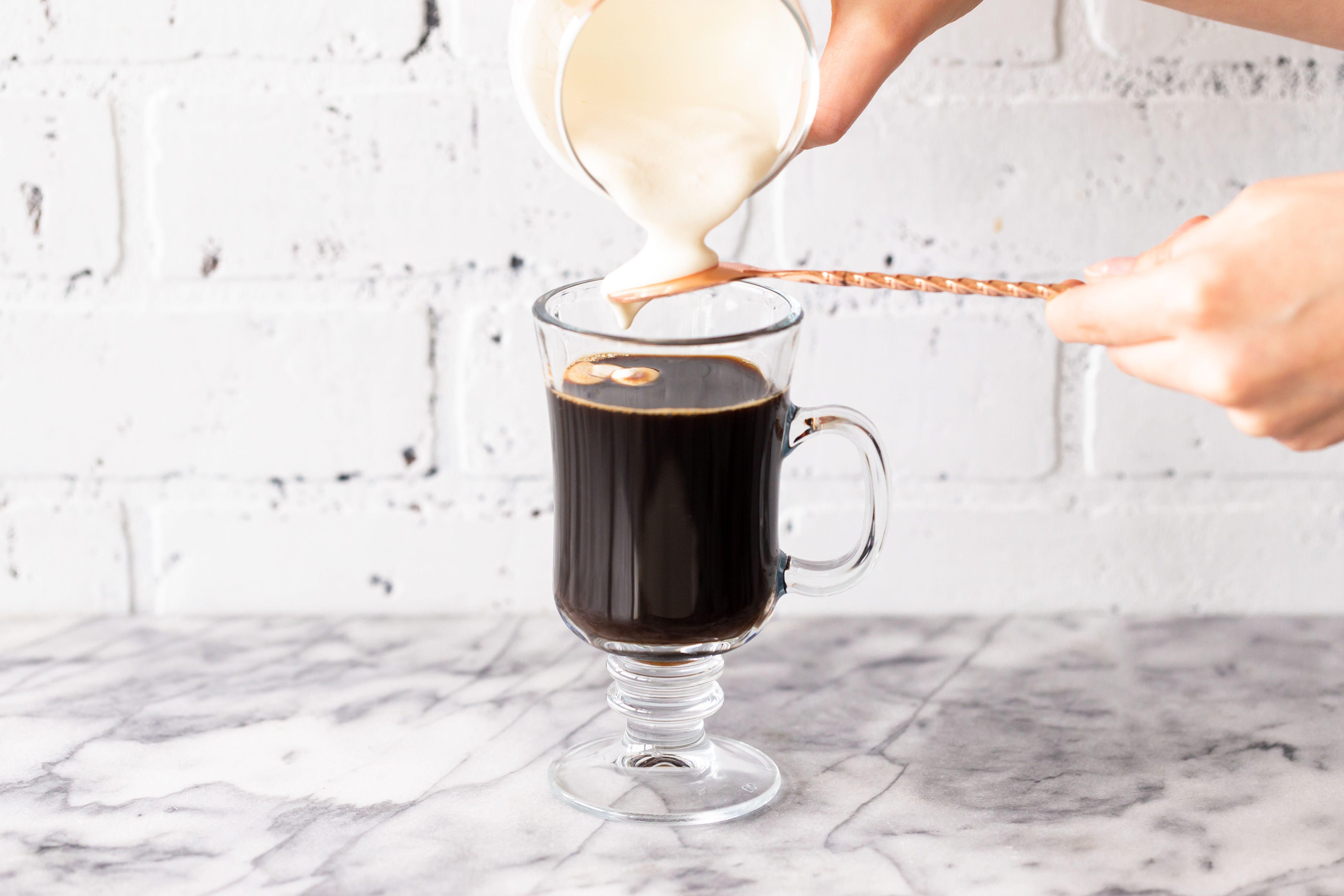 Pour cream over a spoon into Irish whiskey
