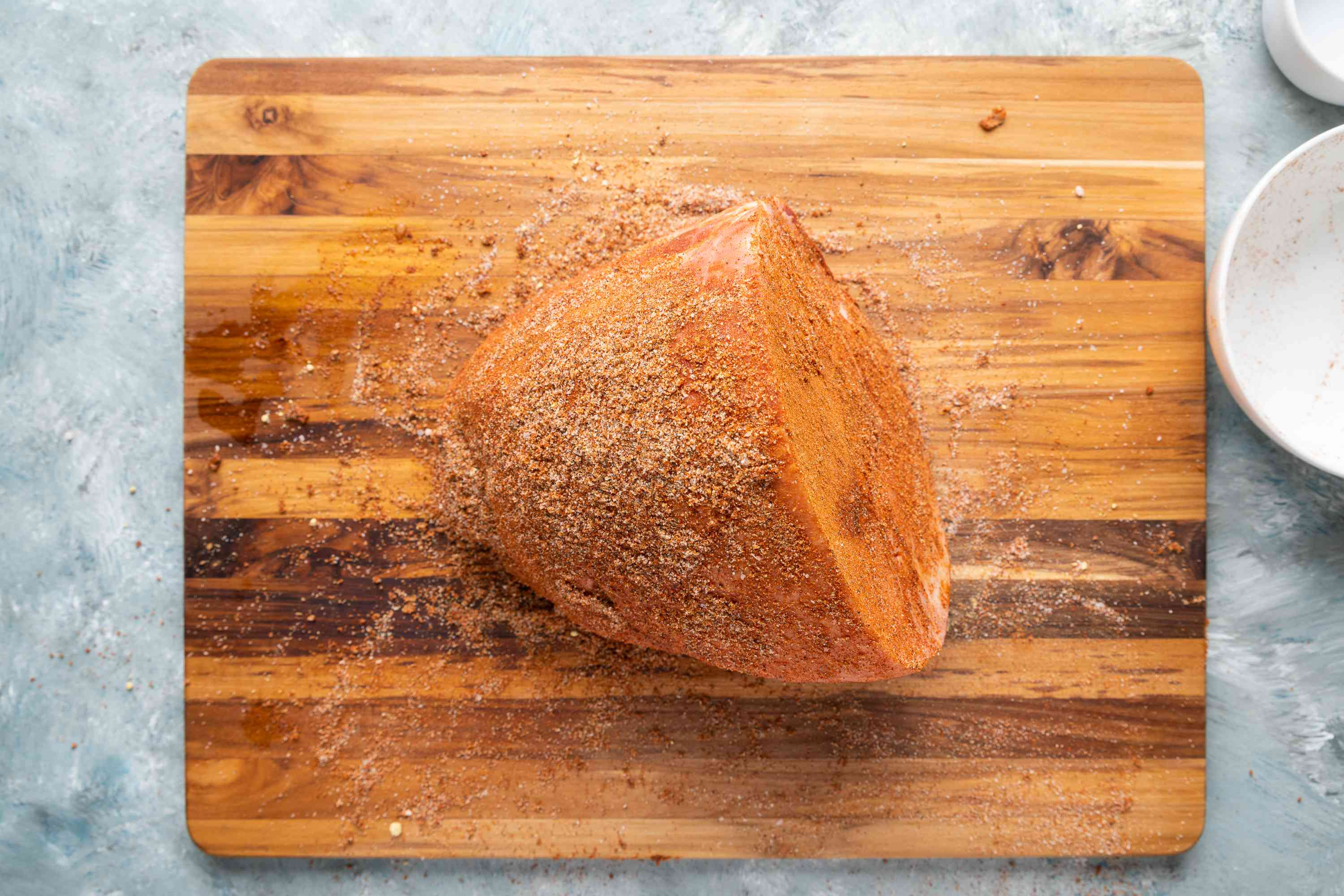 Ham covered with dry rub on a wooden cutting board