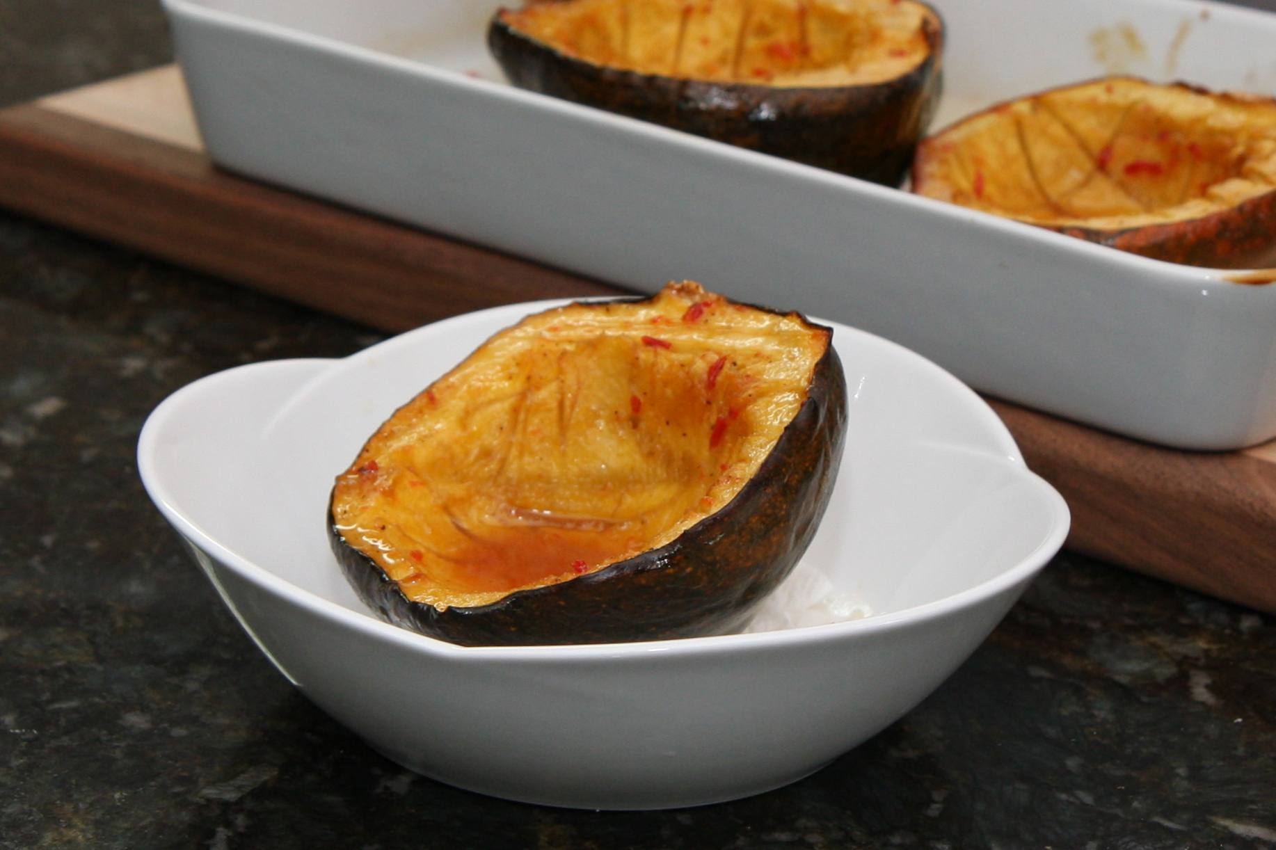 A baked glazed acorn squash in a serving bowl