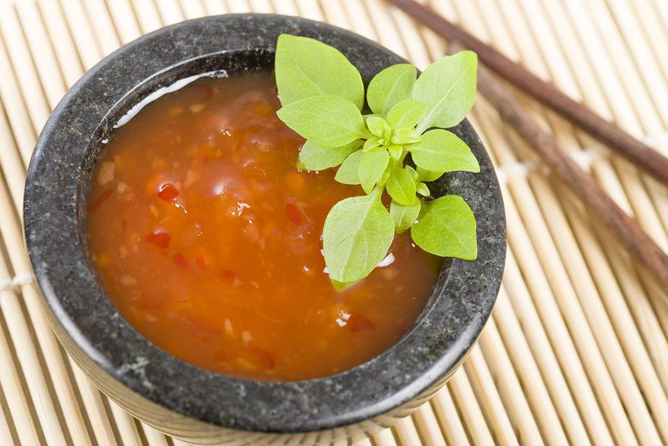 Thai sweet chili sauce in a bowl garnished with Thai basil.