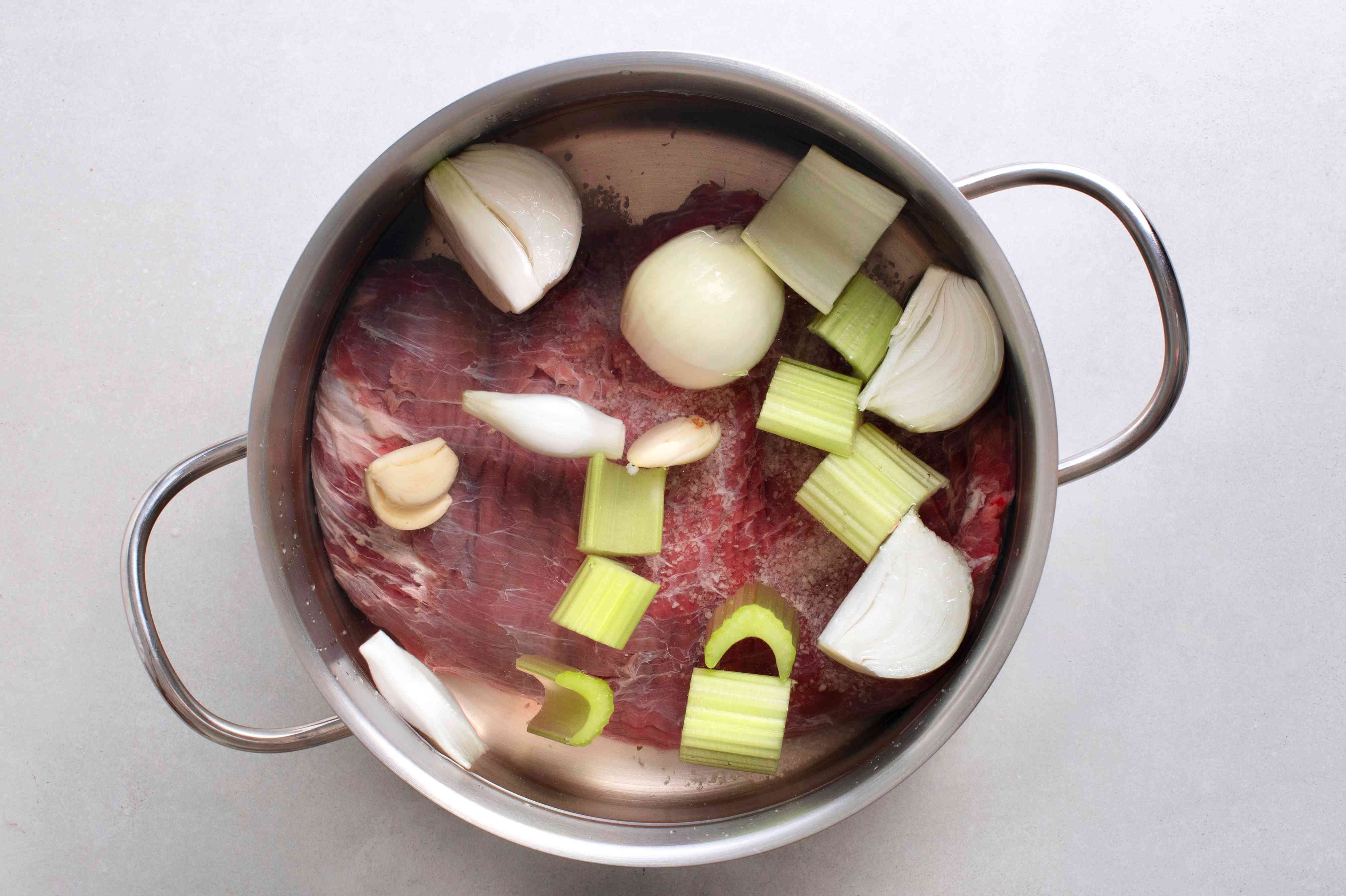 Add the quartered onion, smashed garlic, chopped celery, and salt to the steak in the pot