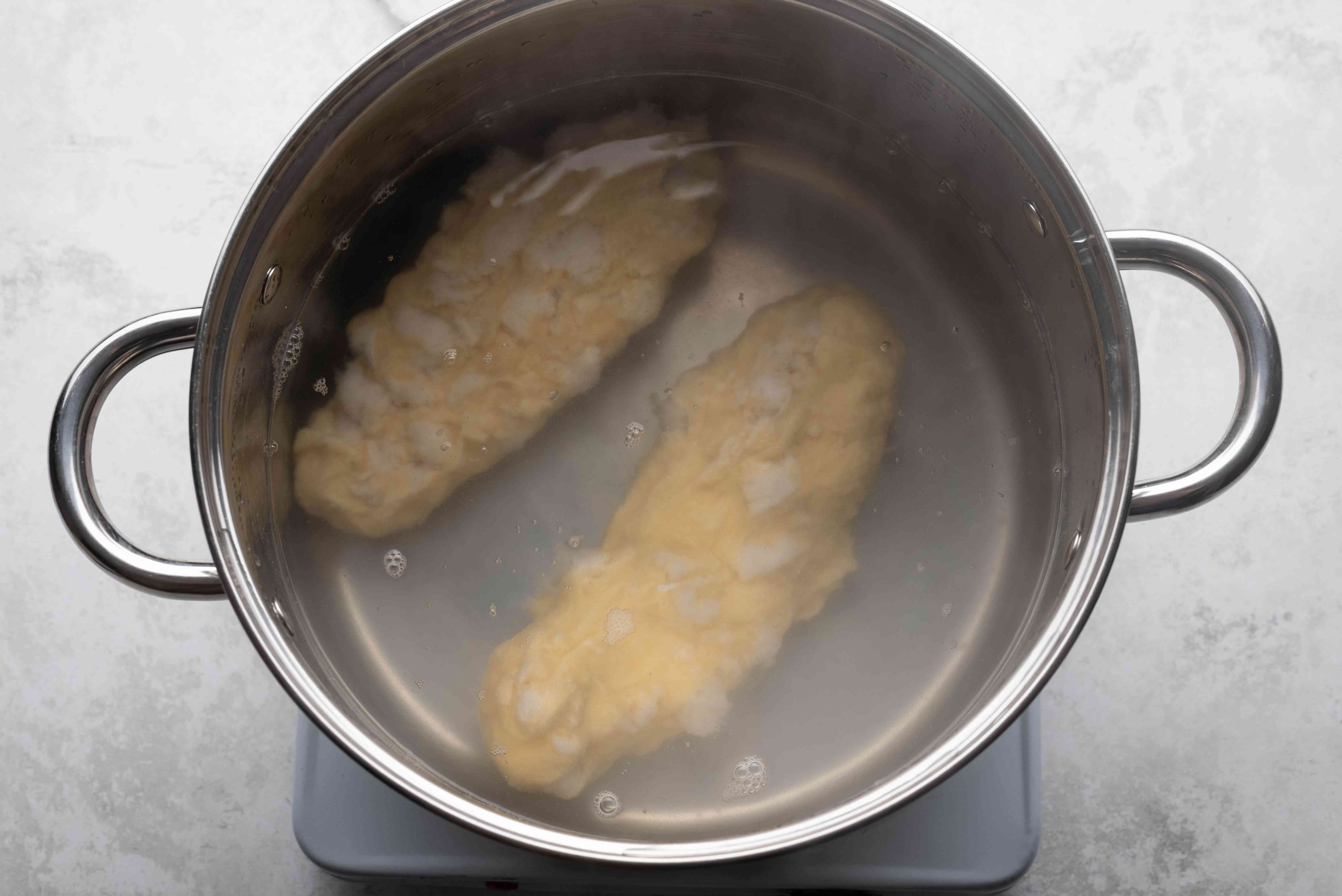 Rolls of dough in a pot with boiling water