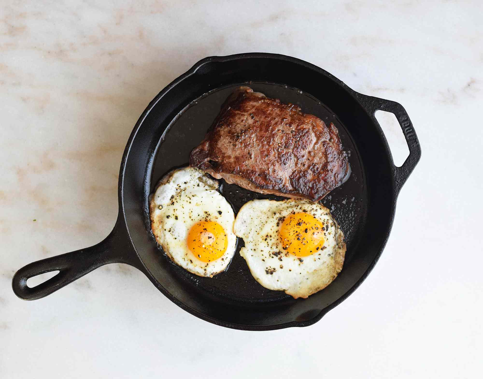 Steak and eggs cooking in a pan