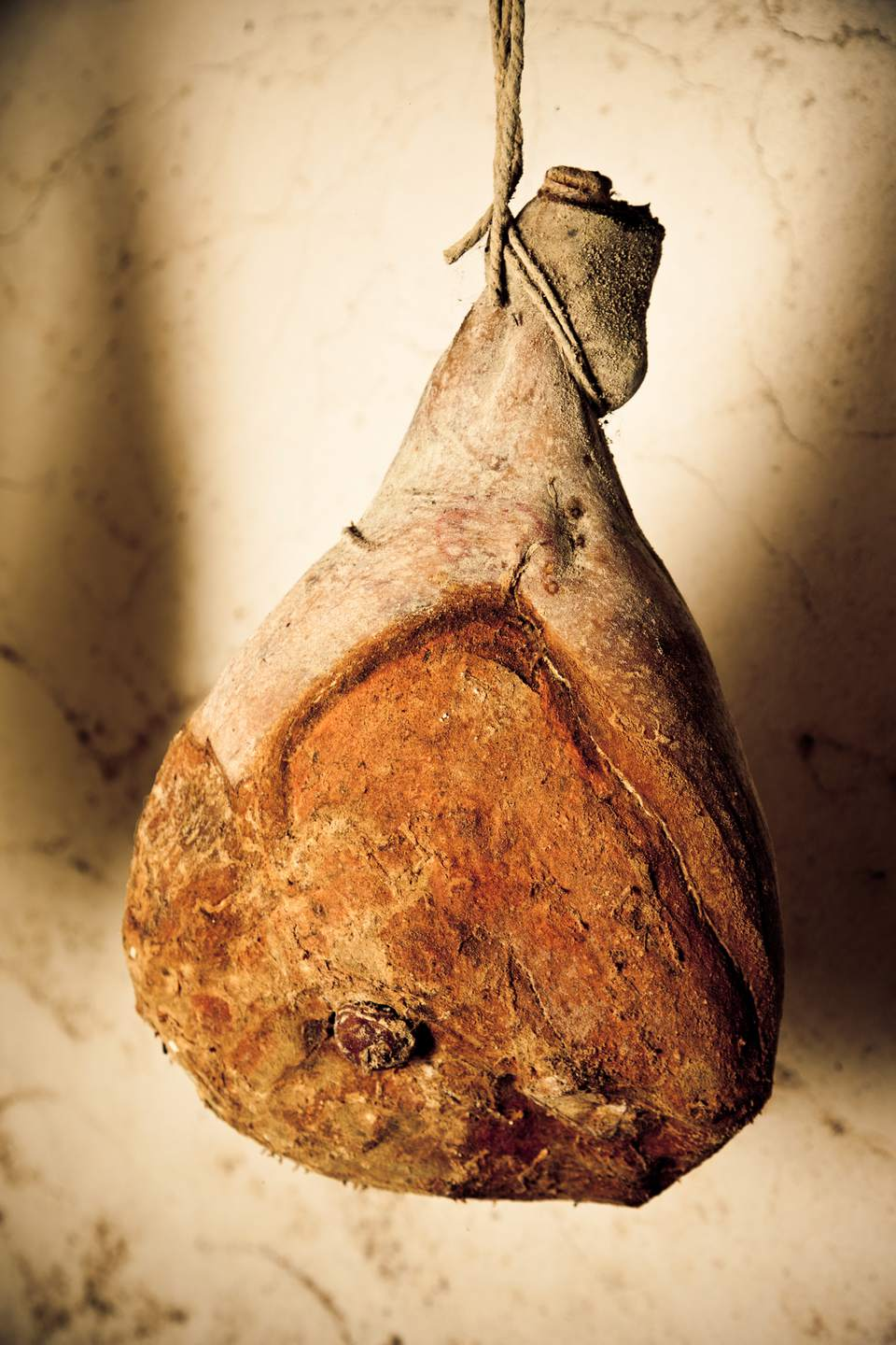A prosciutto hanging to cure in a basement