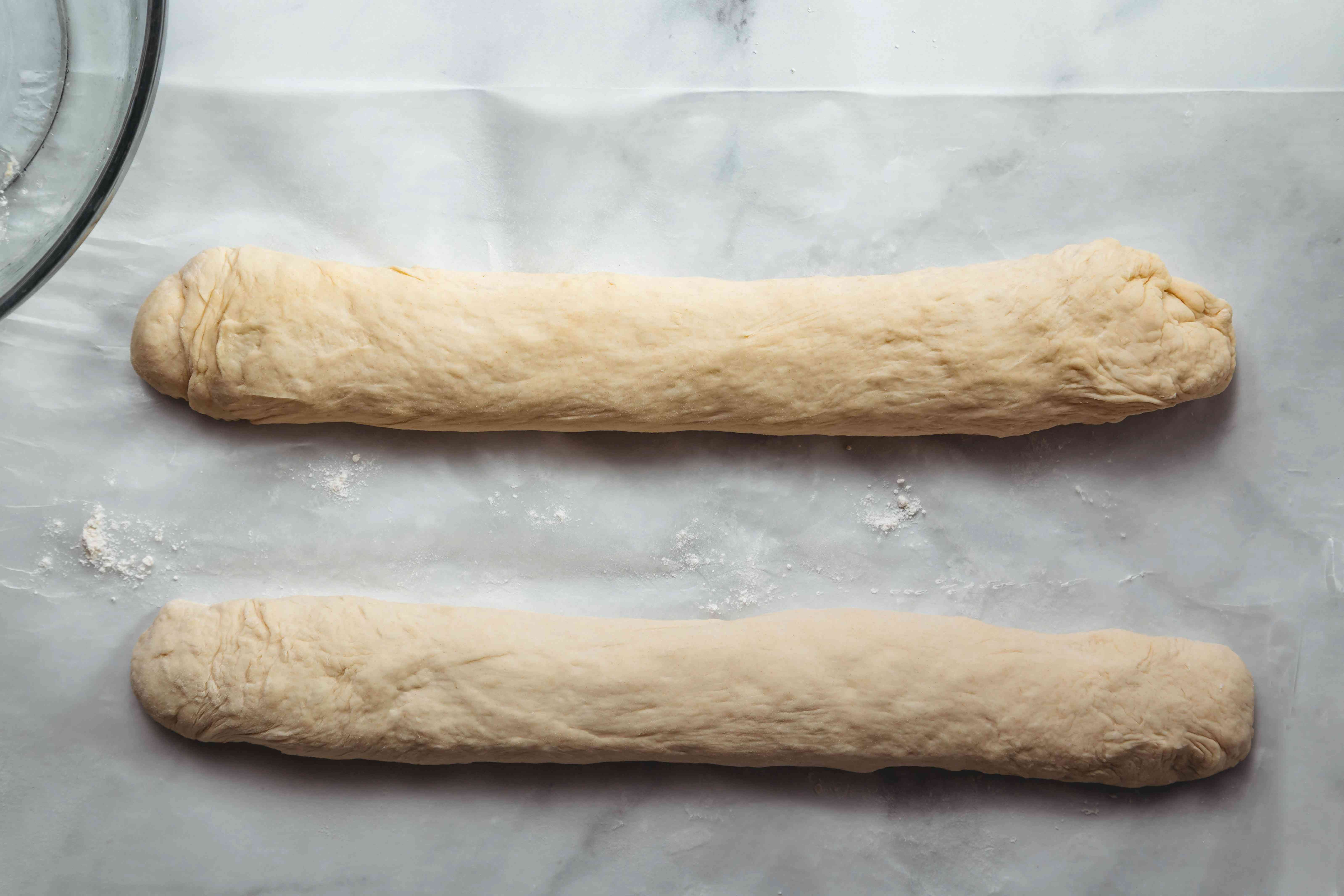 Two dough logs on a floured surface