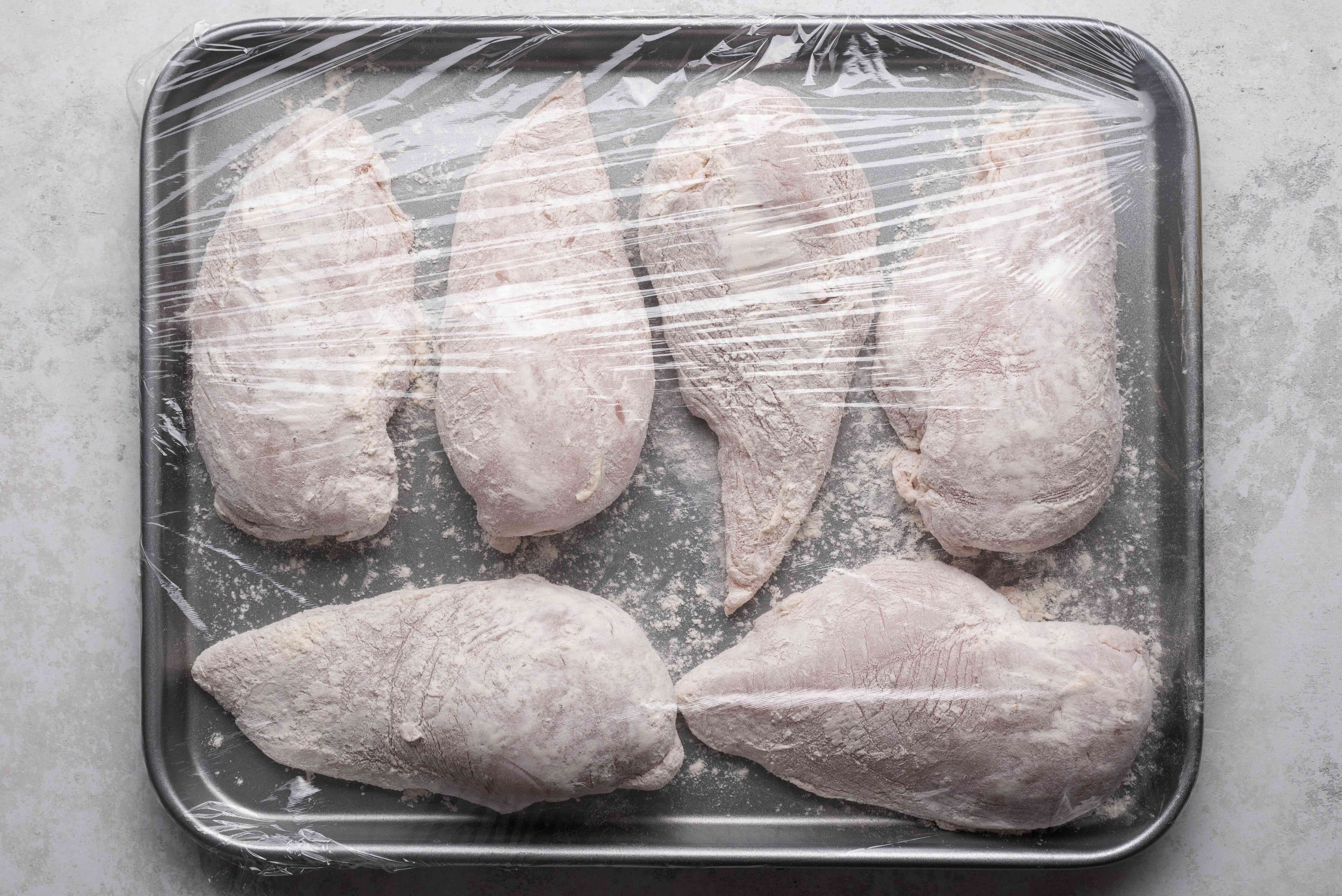 chicken on a baking sheet covered with plastic wrap