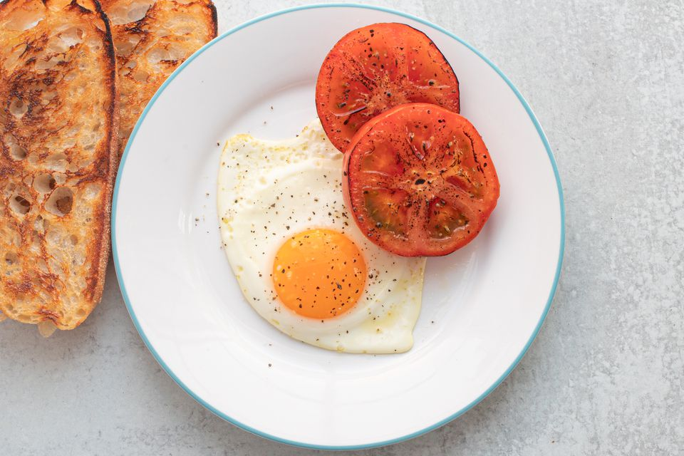 Sunny-side up egg on a plate with charred tomatoes.