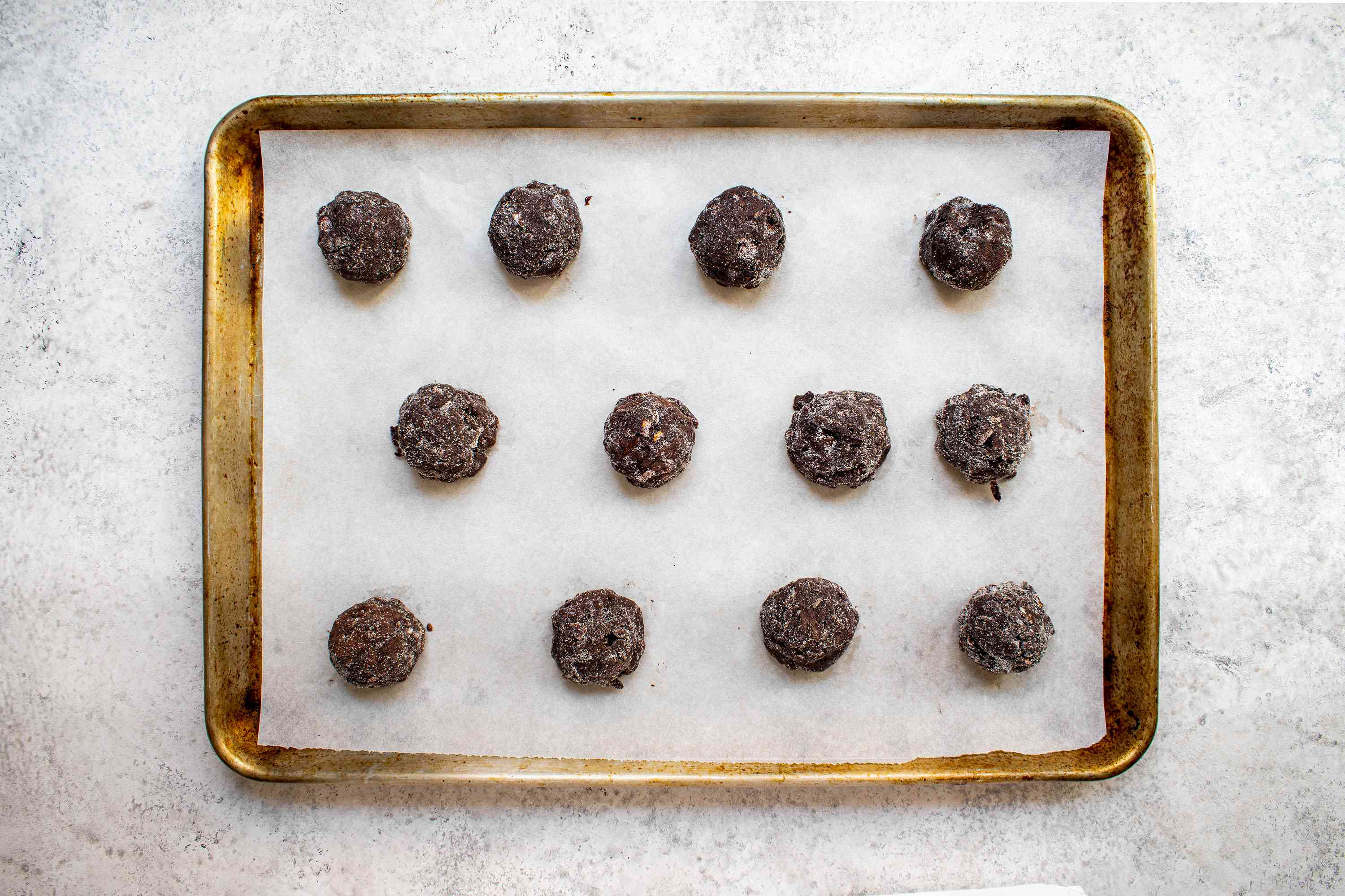 cookie dough balls rolled in sugar on a parchment paper lined baking sheet