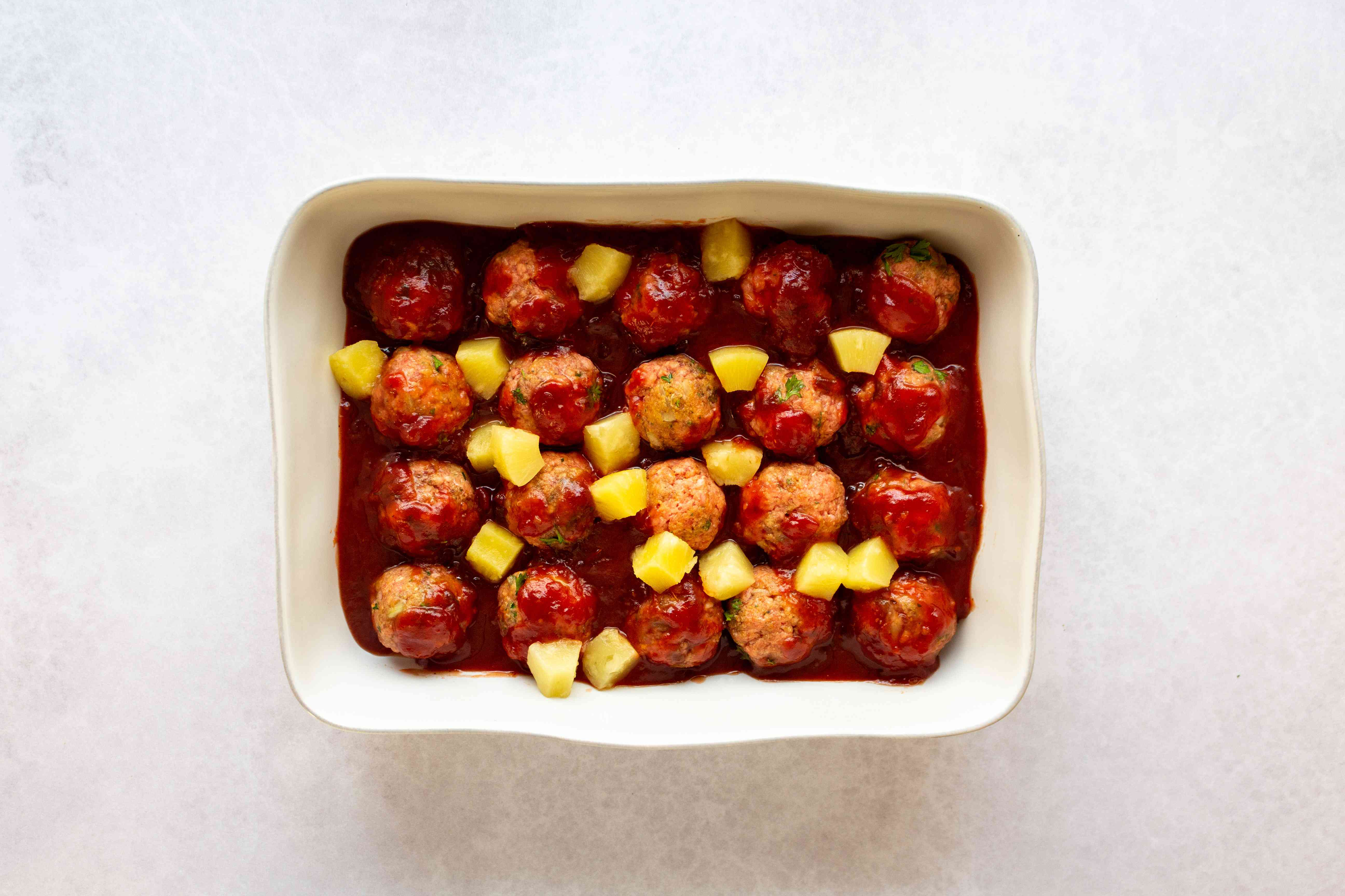 meatballs with sauce and pineapple chunks on top