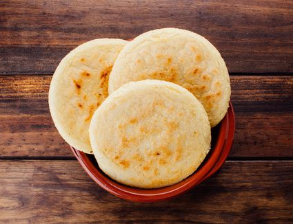 Plate with arepas on a rustic wooden background