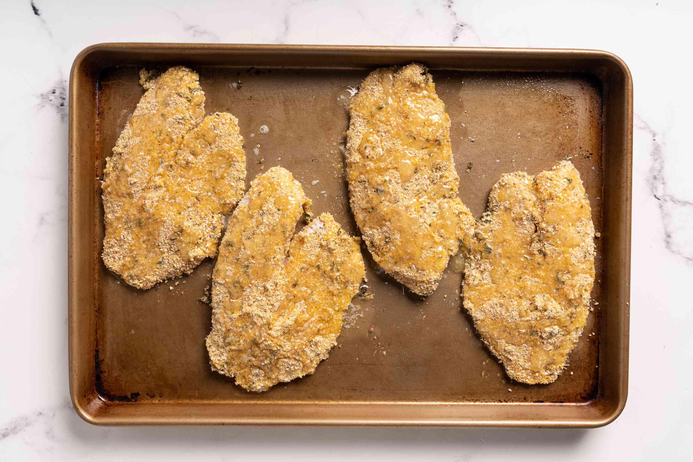 breadcrumb coated tilapia on a baking sheet