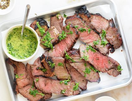 grilled chuck roast sliced on a tray with chimichurri