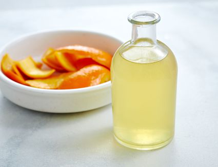 Orange simple syrup in a glass jar, with oranges