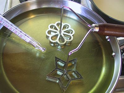 oil and rosette irons in a frying pan with a thermometer