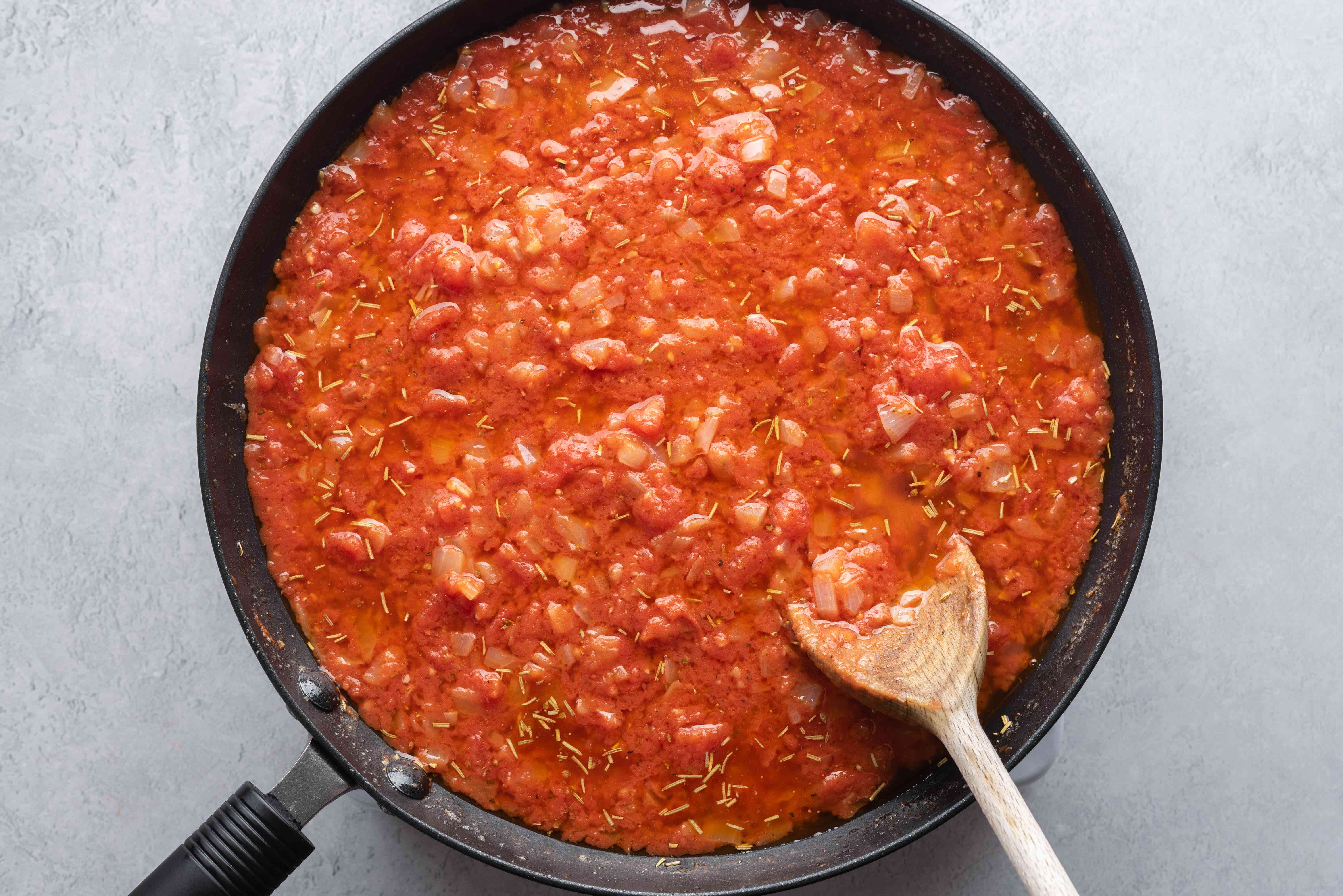 Add tomatoes, spices, salt, and pepper to the onion mixture in the pan