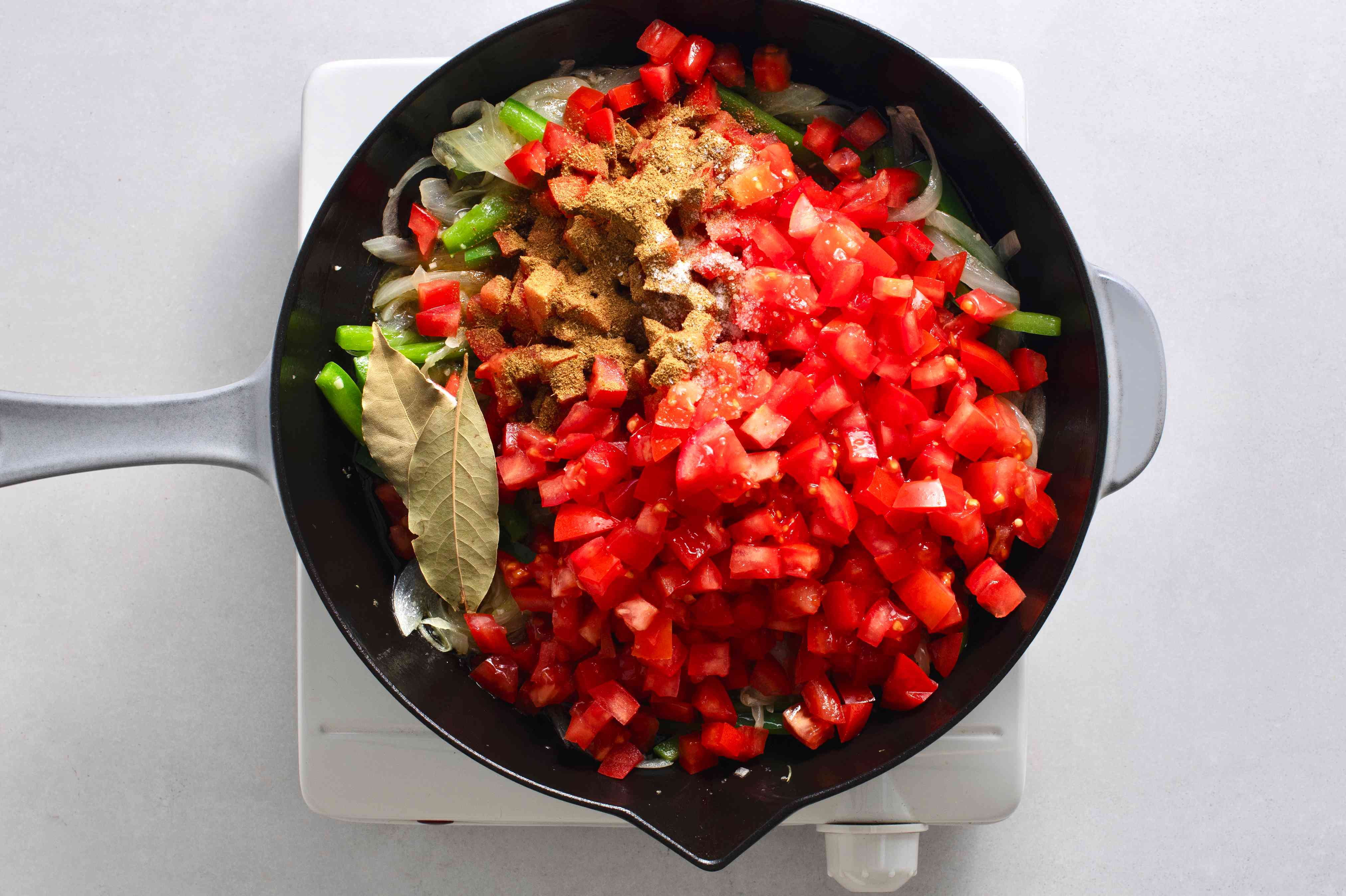 add tomatoes and spices the onion and pepper mixture in the skillet
