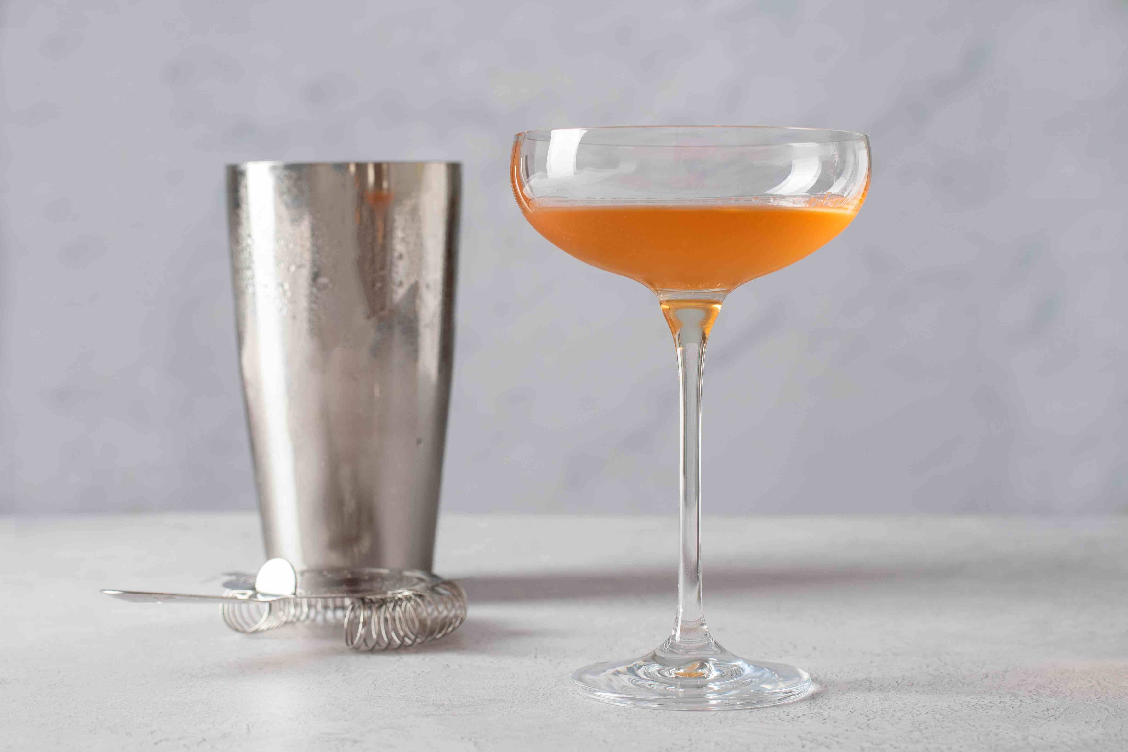 strain pink gin cocktail into a glass
