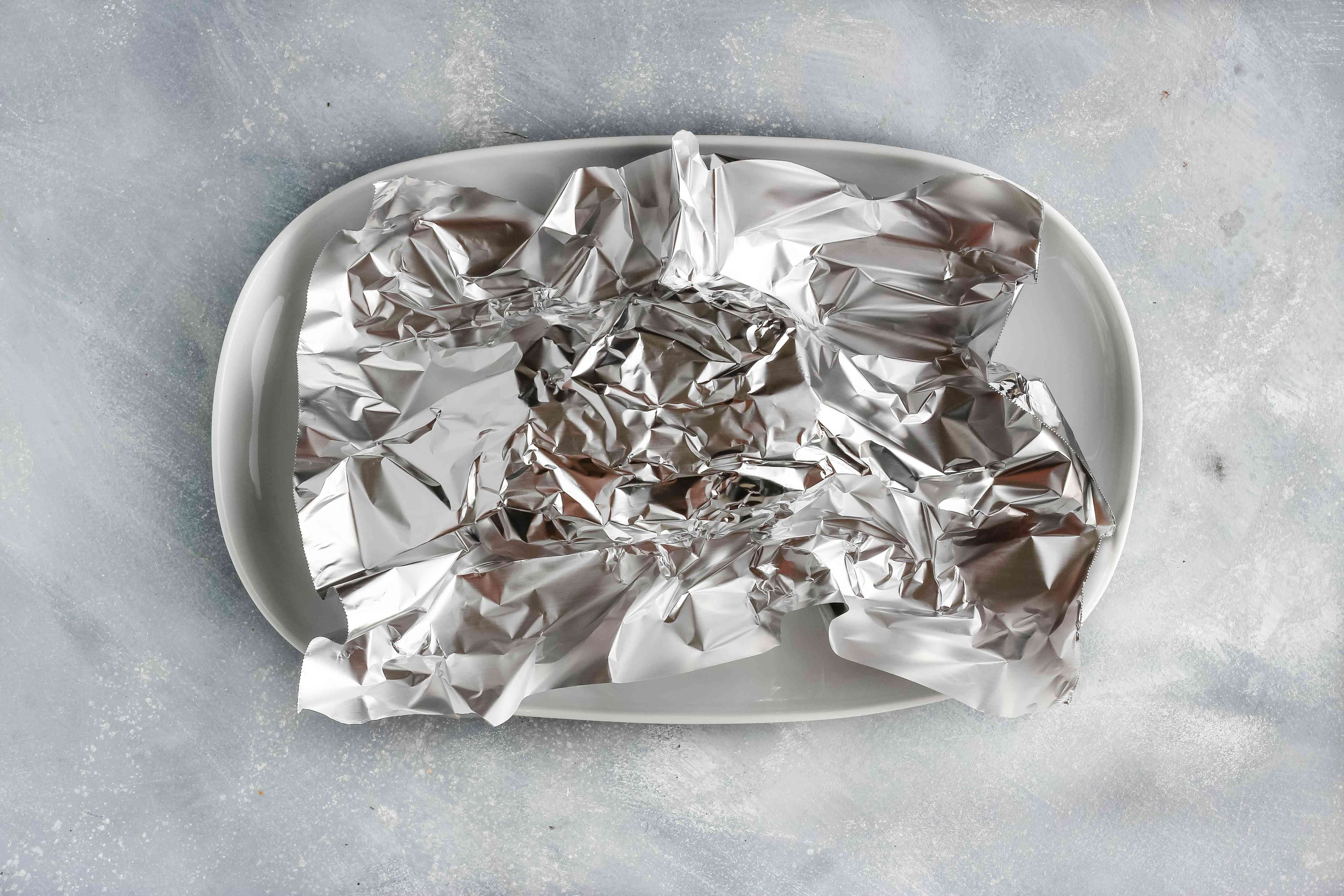 The meat is on a plate tented with foil