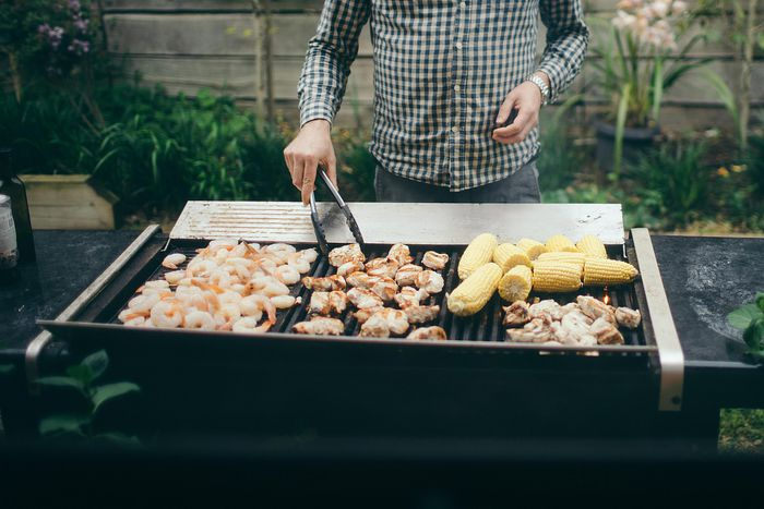 Man grilling chicken, corn and shrimp