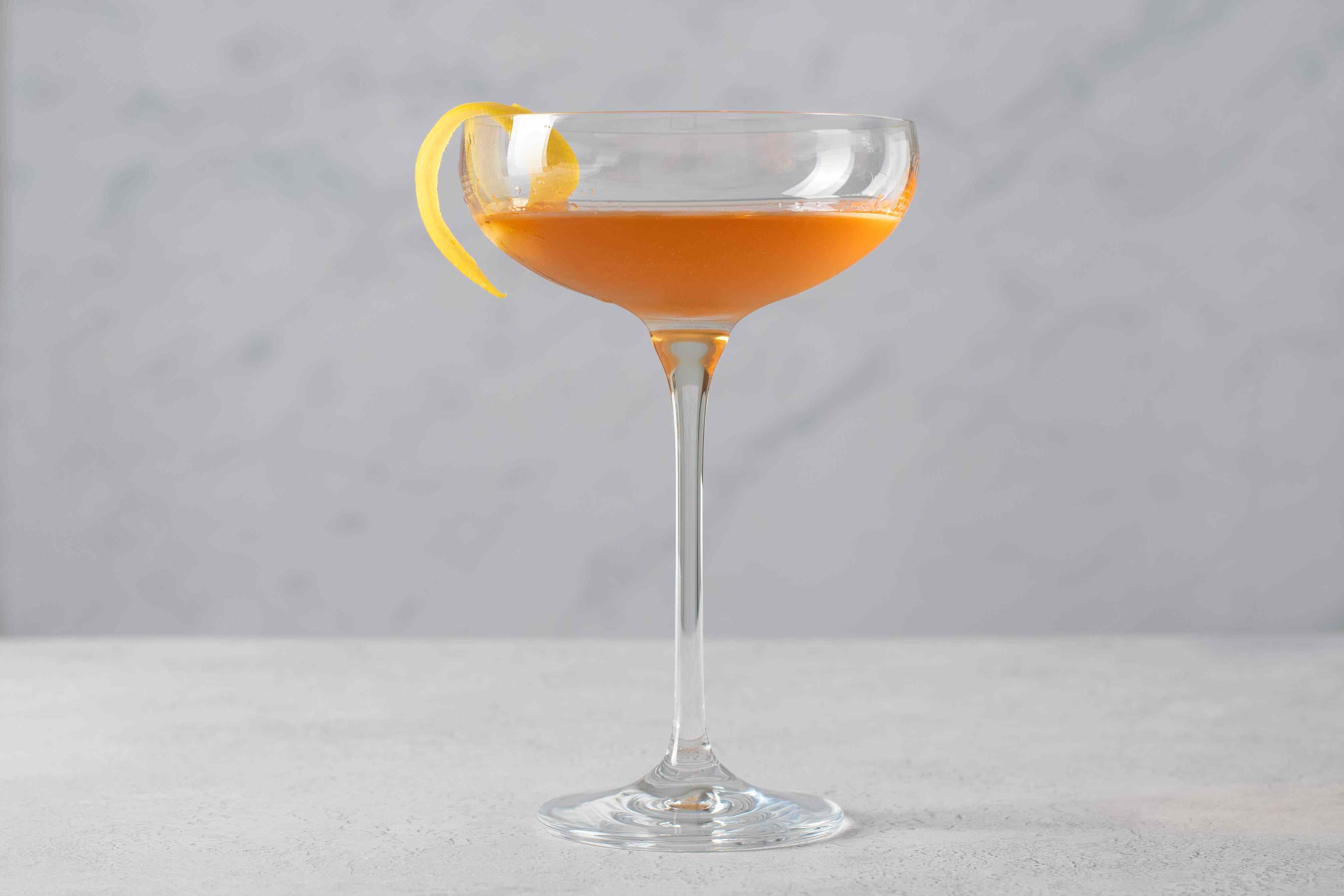 Pink Gin cocktail garnished with lemon twist