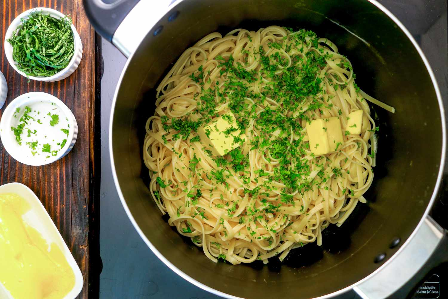 Butter, parsley, and basil are added to pasta and tossed