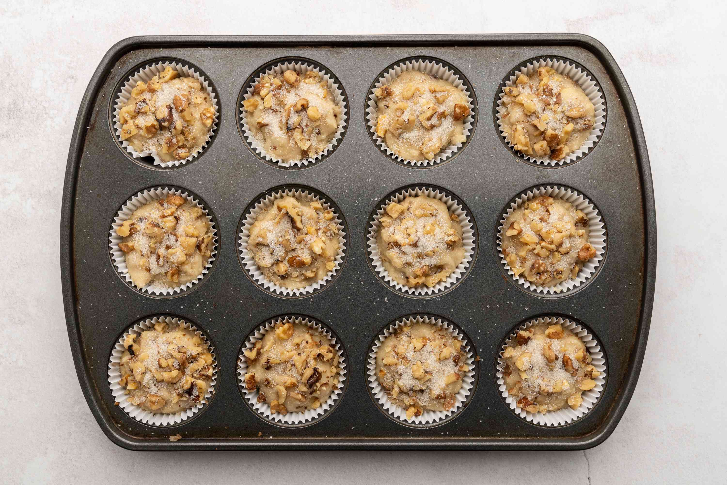 Banana bread mixture has been added to a muffin tin lined with paper inserts
