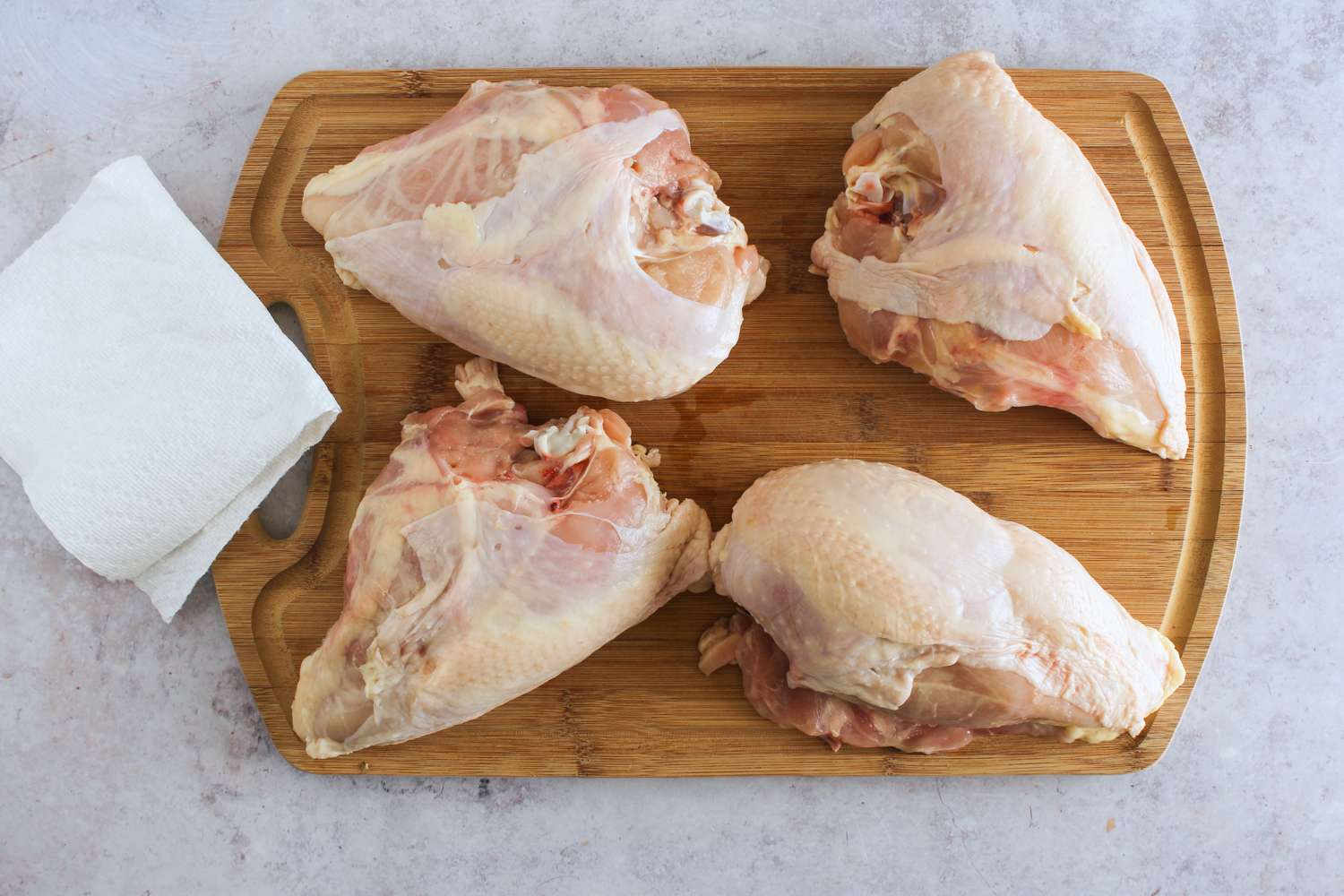 Bone-in chicken breasts pat dry with a paper towel on a cutting board