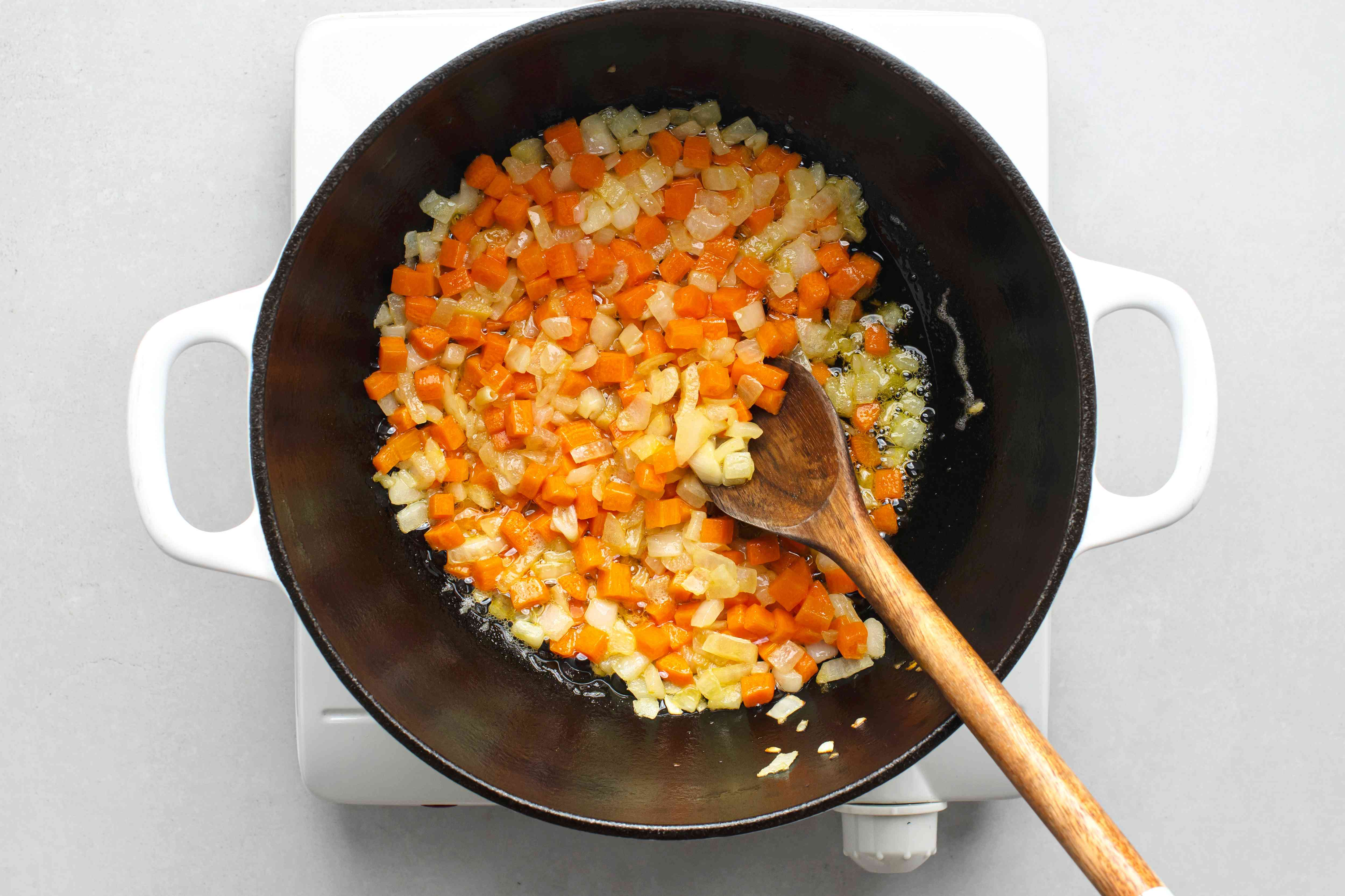 Dutch oven with butter, carrots and onions