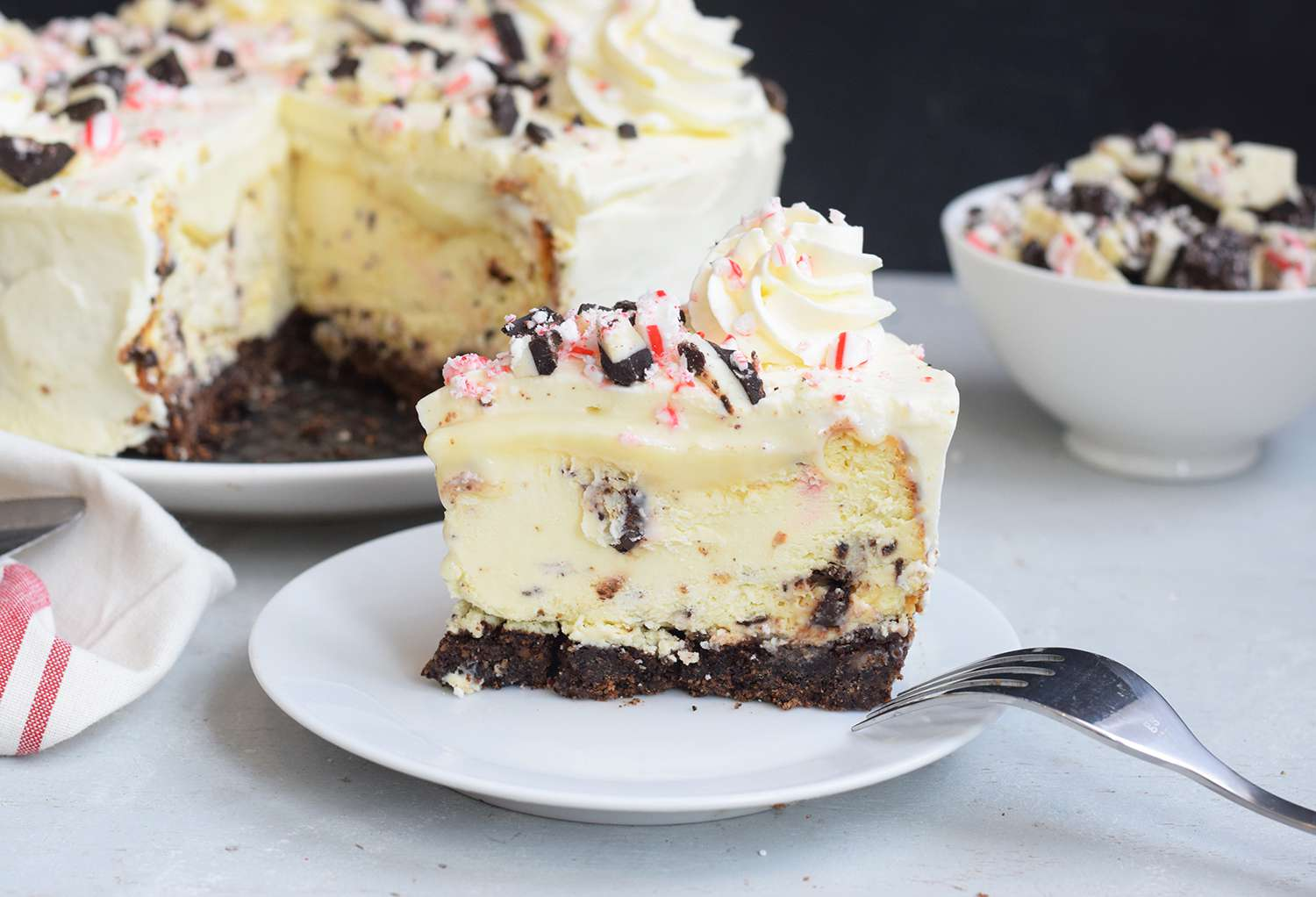 Peppermint bar cheesecake slice on a serving plate