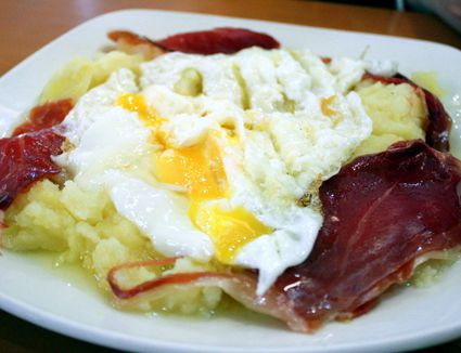 A plate of huevos rotos, fried eggs and Spanish meat