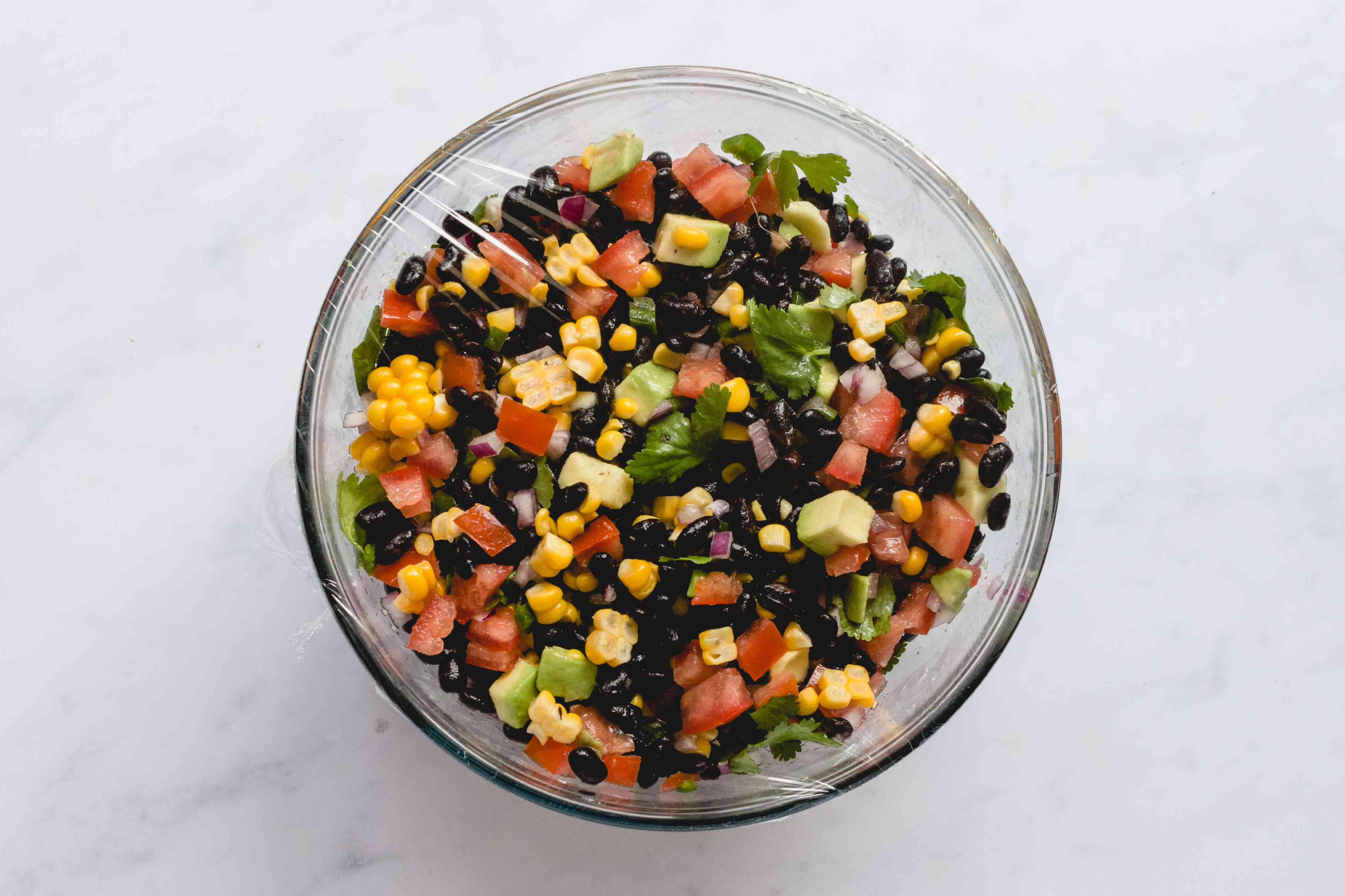 Easy Black Bean Salad in a bowl covered with plastic wrap