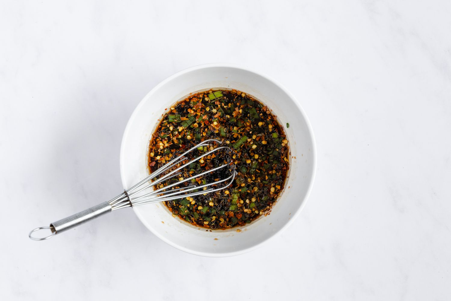Whisk in the ginger, garlic, scallions, brown sugar, and crushed red pepper into the soy sauce mixture