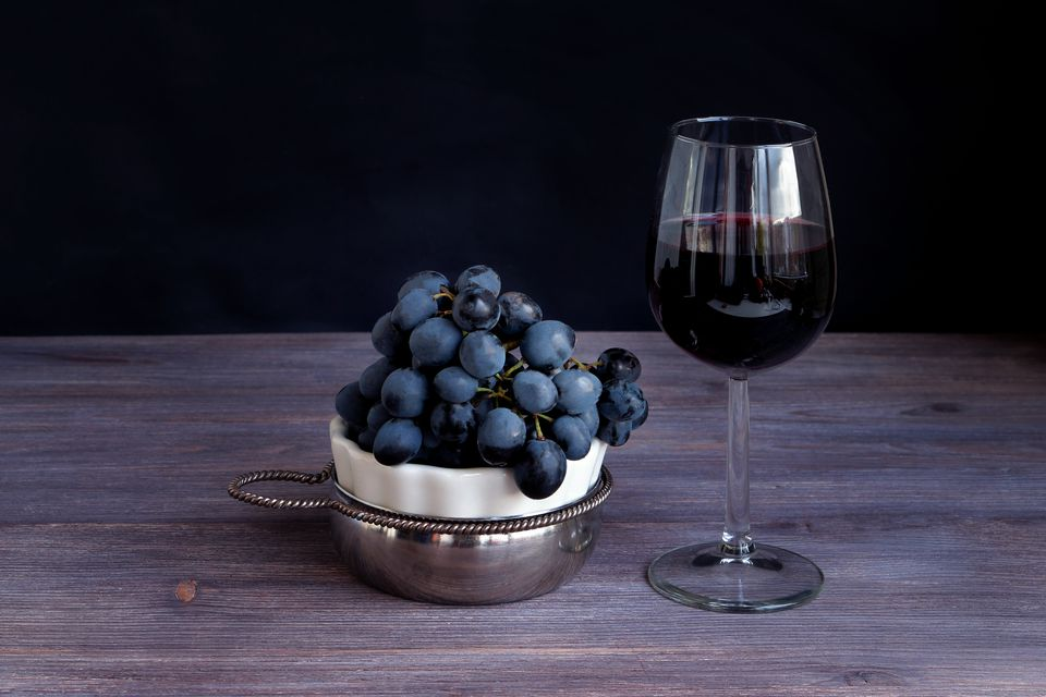 Sangiovese in wine glass, bunch of dark purple grapes