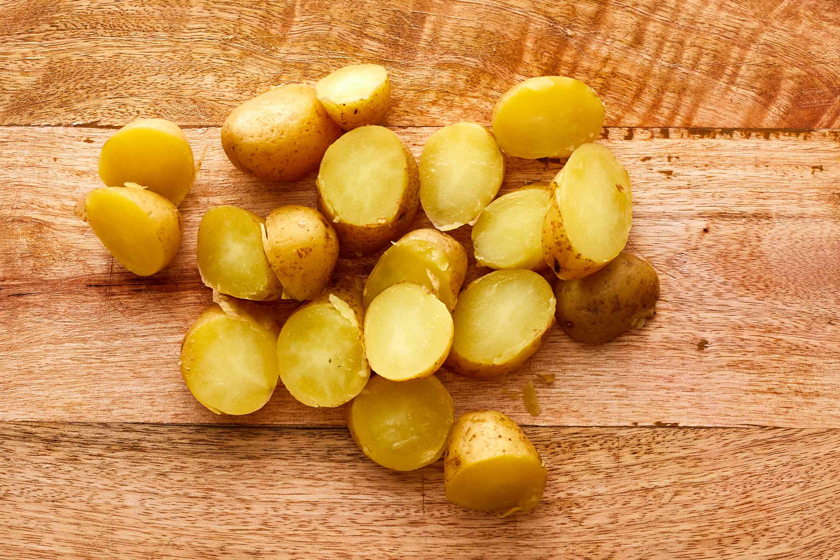 Cooked potatoes on cutting board cut in half