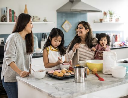 2 mothers with children makings cupcakes in kitchen
