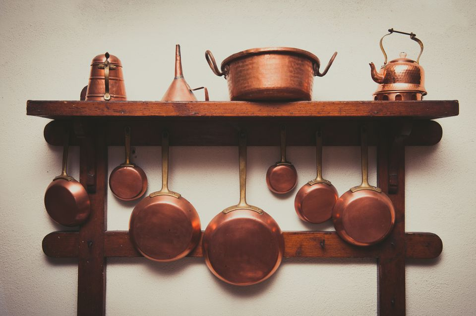 Copper Kitchen Utensils Arranged On Shelf In Kitchen