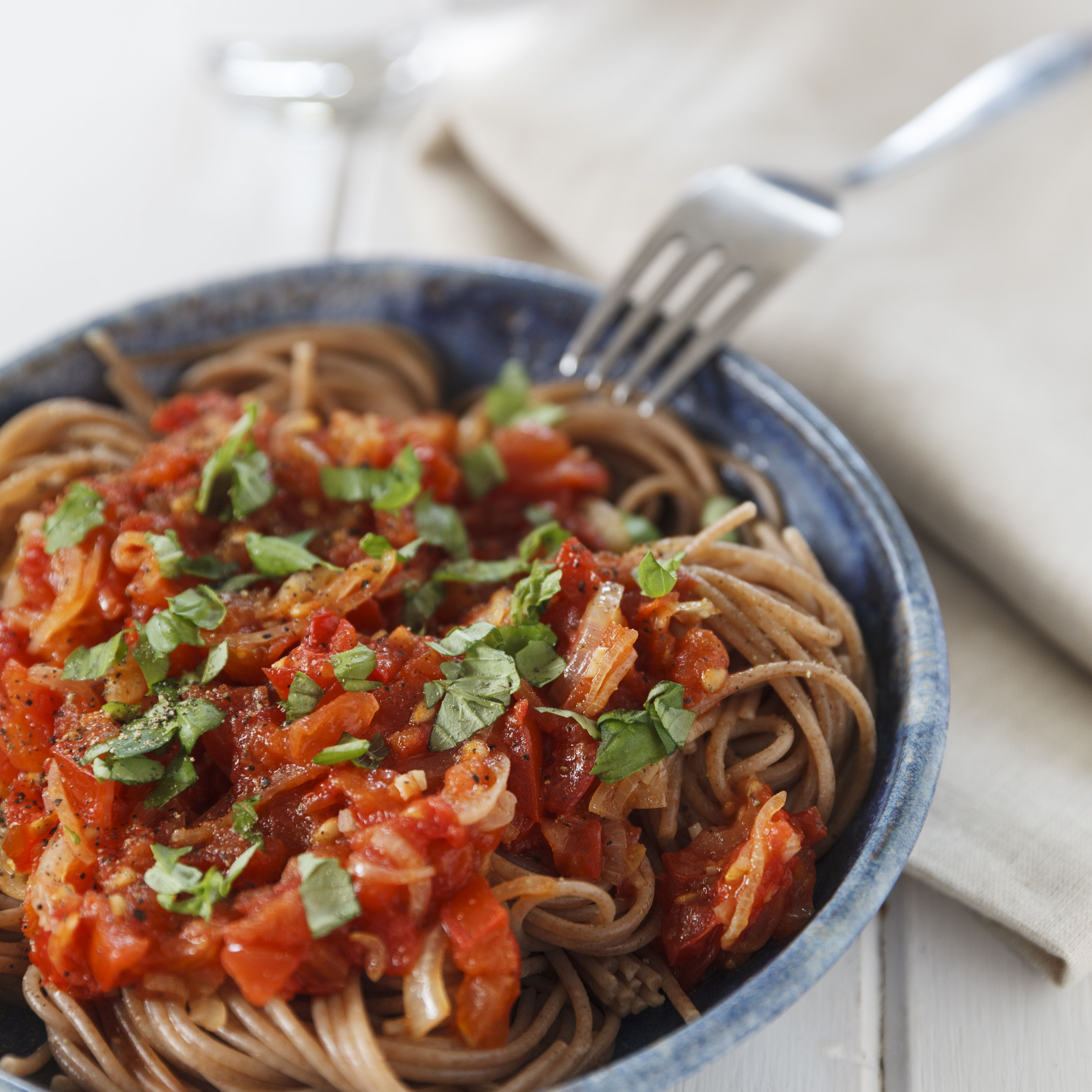Bowl of spelt pasta with tomatoes and basil, close-up