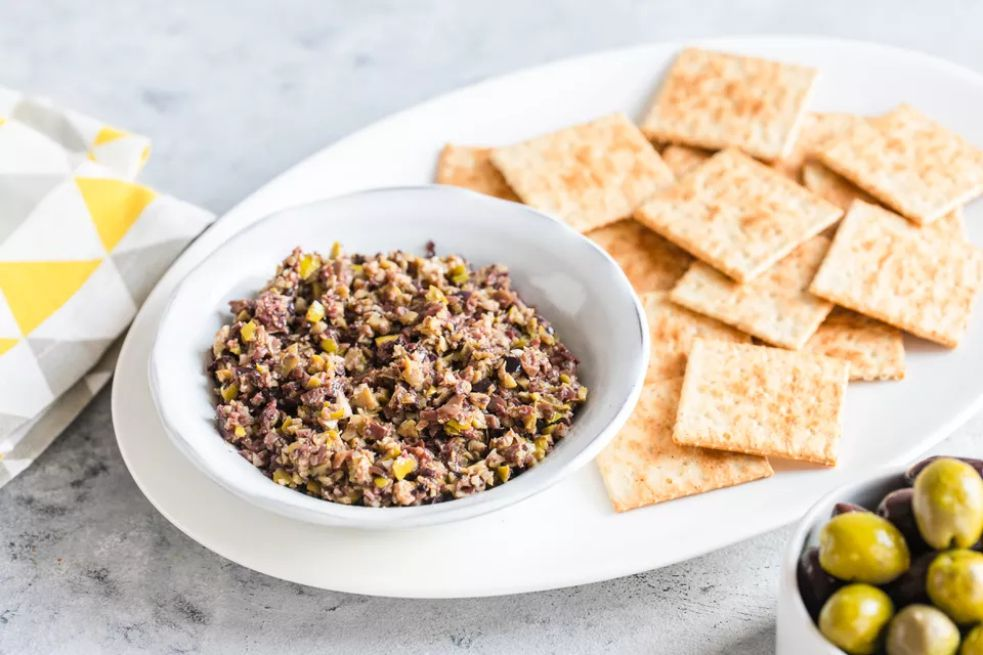 Vegan olive tapenade with crackers and olives