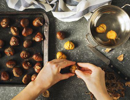 Hands peeling roasted chestnuts