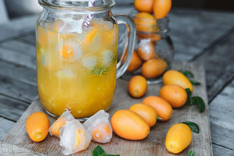 Glass jars of orange juice with ice and kumquat on wooden table