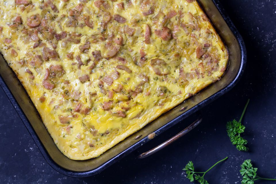 Cheesy bacon and sausage breakfast bake in oven tray on black background - Savory tart